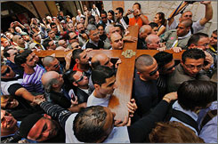 Christian worshipers carry a cross through Old City in Jerusalem on Good Friday and make their way toward the Church of the Holy Sepulcher, believed to be the site where Christ was crucified.