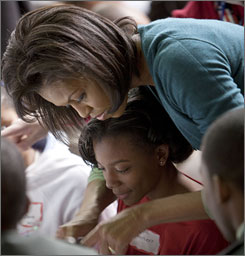 Michelle Obama helps a girl at D.C.'s Calvin Coolidge High School work on a project to support the troops. President Obama and his wife visited the school to promote his Day of Service program Jan. 19.
