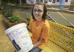 Brooklyn Myers, 14, of Greenville, S.C., poses with a bucket that she made to raise money for Shriners Hospital. She and her mother Bridget Myers have collected $92 in the past two days and hope to raise awareness for the need of donations to the Greenville Shriners Hospital fund.