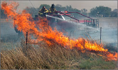 Two people have died in wildfires that have hit Texas and Oklahoma. Here, firefighters battle flames in Wichita Falls, Texas, on Thursday.