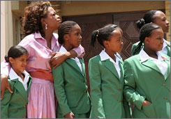 Oprah Winfrey, second left, and several students stand together during the opening of the Oprah Winfrey Leadership Academy for Girls in the small town of Henley-on-Klip, South Africa in Jan. 2007. The school has been rocked in two separate sexual scandals since its opening.