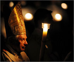 Pope Benedict XVI walks into the darkened St. Peter's Basilica in Rome during the Easter vigil mass on Saturday evening. The candle symbolized hope.