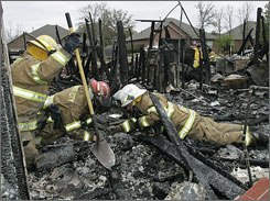 Firefighters, from left, Mike Musshefen, Tim Lawson and Captain Mark Zeckser search for a resident's rings in a home destroyed by fire in Midwest City, Okla., on Friday.