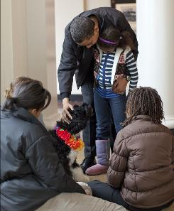 President Obama holds his daughter Sasha as the family meets its new dog, Bo, a 6-month-old Portuguese water dog.
