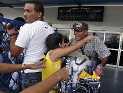 Cubans welcome relatives arriving from the USA at Havana's Jose Marti airport Monday. President Obama eased the way for U.S. telecommunication companies to do business with Cuba and relaxed restrictions on travel to the communist-ruled island.
