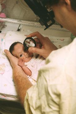 A premature infant with retinopathy of prematurity is examined by a pediatric opthamologist.