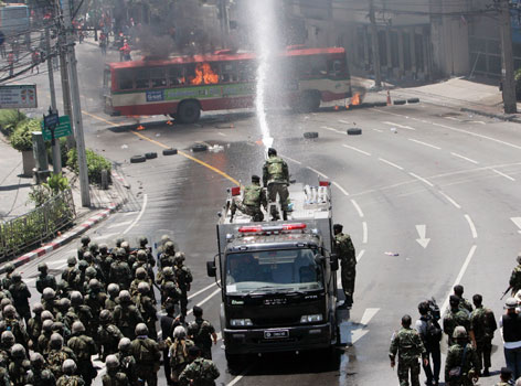 Thai soldiers attempt to control a fire on a bus during clashes with anti-government protesters in Bangkok on Monday.