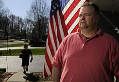 John Cronkwright, 40, a civil engineer from Liverpool, N.Y., shown with son Chase, 9, says government should let the auto companies fail under market pressure, if they're steering that way.
