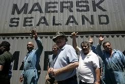 Crewmembers of the Maersk Alabama wave Monday during a news briefing in Mombasa, Kenya. U.S. Navy snipers rescued the crew's captain, Richard Phillips, from pirates on Sunday after a five-day standoff about 20 miles off the Somali coast.