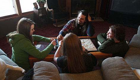 Patrick and Melissa Wojtowicz play Scrabble with daughter Gabrielle, 15, left, and her friend Brittney Watson, foreground. They've made family time a higher priority.