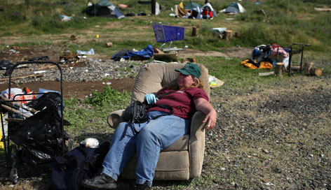 Karen Hersh, a homeless woman, takes a break from packing her belongings at Sacramento's tent city Wednesday after the city ordered all to relocate to a nearby shelter.