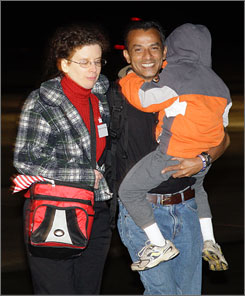 Maersk Alabama crewmember Zahid Reza is reunited with his wife and child at Andrews Air Force Base in Maryland on Thursday.