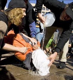 Protesters demonstrate waterboarding, an interrogation technique that simulates drowning, Nov. 5, 2007, on volunteer Maboud Ebrahim Zadeh in front of the Justice Department in Washington.