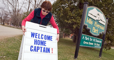 Livy Strong, chairperson of the Jericho Underhill Park District, sets up a sign at the Mills Riverside Park in Underhill, Vt., to welcome Capt. Phillips back home.