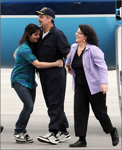 "Captain Richard Phillips steps off a plane and is hugged by his daughter and followed by wife. ""We did it. We did what we were trained to do,"" he said later after a private reunion with his family."
