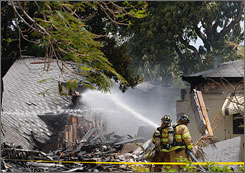 Firefighters hose down the scene Friday in Oakland Park, Fla., outside Fort Lauderdale, where a small plane crashed into a home in a residential neighborhood.