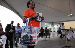 A woman holds a bag bearing the likeness of President Obama as she attends a program in Port of Spain, Trinidad, on Thursday for participants of the upcoming Summit of the Americas. Obama is due to arrive in the country Friday for the meeting.