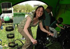 A woman pedals a stationary bike at an energy exhibit Sunday during an Earth Day event on the National Mall in Washington, D.C. The festivities were organized by the Earth Day Network.