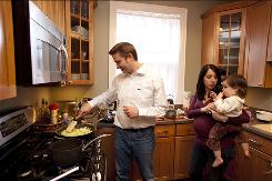 Chris Burns, 34, cooks dinner with his pregnant wife, Becky, and their daughter, Caitlin, 17 months. Burns lost 32 pounds using MyNetDiary, an iPhone application that tracks calories.