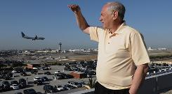 Neighborhood activist Denny Schneider, president of the Alliance for a Regional Solution to Airport Congestion, watches air traffic atop a building near Los Angeles International Airport.