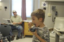 Watson Jones, 6, who is allergic to peanuts, takes a peanut protein mixed with applesauce under the watchful eye of his father, Charles Jones, at at the Duke University Medical Clinic in Durham, N.C.