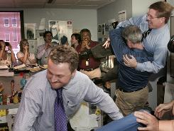 Detroit Free Press reporter Jim Schaefer, right, lifts Senior Managing Editor Jeff Taylor as reporter M.L. Elrick, left, celebrates the newspaper's Pulitzer Prize for local reporting.