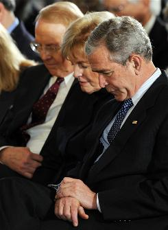 President Bush bows his head in prayer alongside James Dobson, left, founder of Focus on the Family, and his wife, Shirley Dobson, during a National Day of Prayer event in the East Room of the White House on May 1, 2008.