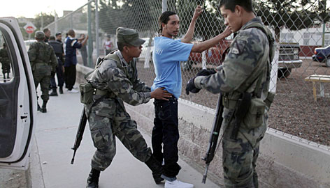 Soldiers frisk a man during a routine patrol in Ciudad Juarez, Mexico, Sunday.