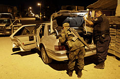A soldier checks the trunk of a car during a routine patrol in Ciudad Juarez, Mexico, late Sunday.