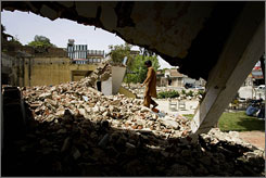 A student walks on the debris of a school building allegedly destroyed by militants in Pakistan's Swat Valley on Tuesday.