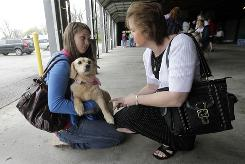 Paige, a 3-year-old Corgi mix, gets to know Erin Rowland, left, and her mother Tanya Rowland, at Indianapolis Animal Care & Control during a Tour For Life adoption event. The Rolwands decided to adopt Paige.