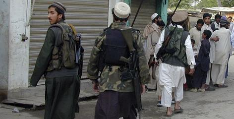 Armed members of the Pakistani Taliban walk on a street in the Buner distric on Thursday, about 60 miles northwest of Islamabad. Pakistani authorities deployed paramilitary troops in a nothwestern district virtually taken over by the Taliban after government ceded to their demand to impose Islamic law, police said.