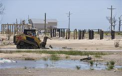 A worker clears debris Wednesday left by September's Hurricane Ike in Crystal Beach, Texas, on the Bolivar Peninsula, where nearly 4,000 homes were destroyed.