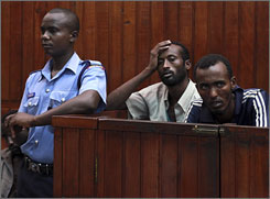 Two of eleven Somali men suspected of piracy sit as charges against them are read out, in a court in Mombasa, Kenya.