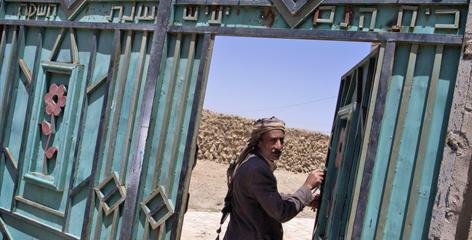 """A Jewish man walks through a metal gate with writing in Hebrew reading """"Yaish Community Center, 1965,"""" which leads to a Jewish girls' school and makeshift synagogue in Kharif, Yemen."""