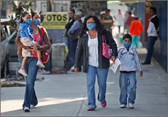 People in Mexico City wear surgical masks as they walk toward the entrance to the General Hospital there. Authorities are looking into whether an illness there that has sickened hundreds is the swine flu.