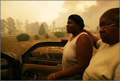 Two women evacuate their neighborhood in Conway, S.C., on Thursday after wildfires threatened homes there.