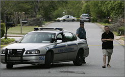 A neighbor passes a police officer standing guard while investigating the Athens Community Theater shooting.