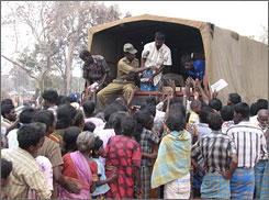 Tamil civilians gather around a truck to receive food at a camp for the displaced.