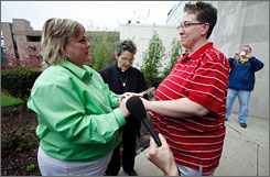 Shelley Wolfe, left, and Melisa Keeton, right, hold hands as Rev. Peg Esperanza performs their wedding ceremony on Monday outside the Polk County administrative building in Des Moines. The couple was the first to obtain a marriage license in the state and be pronounced legally married after the state Supreme Court on Monday issued the final step in clearing the way for such unions.