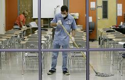 Workers disinfect a classroom at Byron P. Steele High School in Cibolo, Texas, on Monday. Three cases were confirmed in the area, and all 14 district schools were closed.
