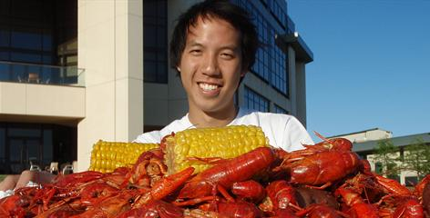 Brian Goh, a biochemistry major with a 4.0 GPA, poses with crawfish and corn on campus at Louisiana State University. Goh rode 2,100 miles from Washington, D.C., to Baton Rouge to raise money for cancer screenings in rural areas.    Click here for full gallery.