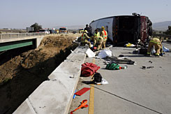 Firefighters investigate the scene of a tour bus crash, Tuesday, on U.S. 101 in Soledad, Calif. The California Highway Patrol reported that dozens were injured in the crash, which occurred shortly before 3:30 p.m.