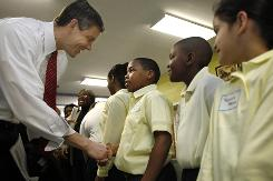 "Secretary of Education Arne Duncan says hello to Antawan Taylor, Trevon York, and Yesnia Mejia at Plummer Elementary School in Washington on April 6. NAEP scores show that achievement gaps between white and minority have barely budged since No Child Left Behind was implemented. Duncan says ""pleased to see some recent progress,"" but ""we still have a lot more work to do."""