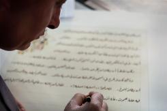 Palestinian calligrapher Yasser Abu Saymeh, a devout Muslim who's spent the past two months writing Christian text, works in his shop in the West Bank town of Bethlehem.