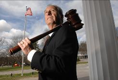Myron Fox, the town moderator in Sudbury, Mass., stands on the steps of Town Hall on April 23.