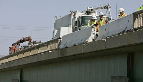 CalTrans workers repair a bridge railing that was damaged during a tour bus accident in Soledad, Calif., on Wednesday.  A bus carrying French tourists through California overturned on a highway overpass in a horrific crash that killed at least five people and left dozens injured.