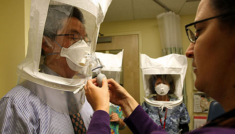 Karya Lustig, right, sprays a chemical mist into a hood Tuesday as she trains doctors and nurses how to use the N95 respirator mask at La Clnica's San Antonio Neighborhood Health Center in Oakland. Many states have declared a public health emergency.