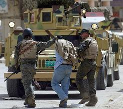 Members of the Iraqi army's intelligence unit detain a sniper suspect from the Sahwa militia in Baghdad last month. 