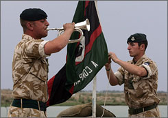 A British soldier plays bugle as he and another soldier lower a flag following their last combat operational patrol near Basra, Iraq, on Wednesday. British troops ended six years of combat operations in Iraq on Thursday.